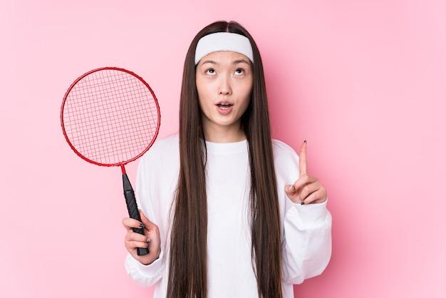 Junge chinesische frau, die badminton spielt