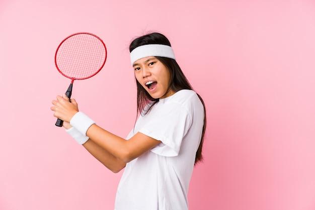 Junge chinesische frau, die das badminton lokalisiert spielt