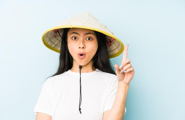 Junge chinesische frau, die ein isoliertes vietnamesisches heu trägt, lacht laut und hält hand auf brust.