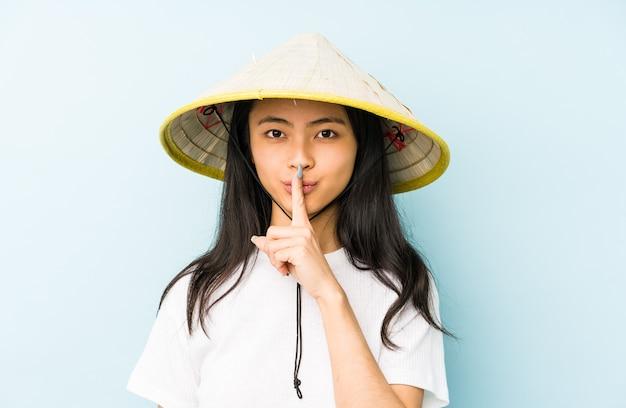 Junge chinesische frau, die ein vietnamesisches heu trägt, das die nummer zwei mit den fingern zeigt.