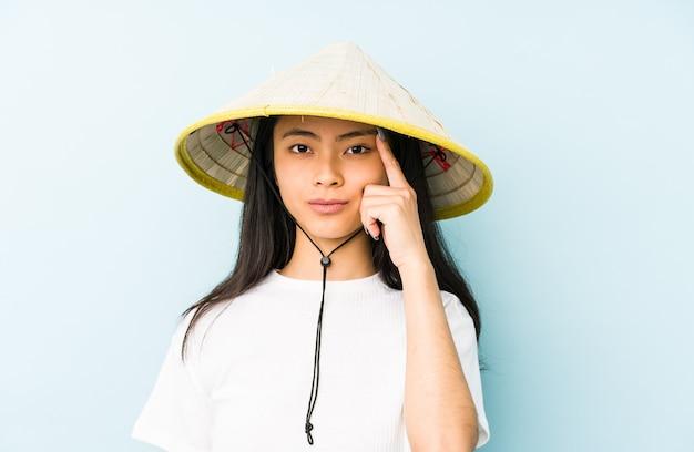 Junge chinesische frau, die ein vietnamesisches heu trägt, das eine enttäuschungsgeste mit zeigefinger zeigt