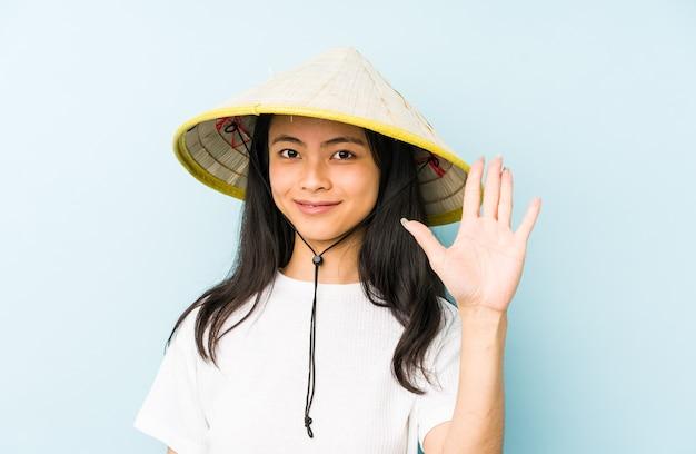 Junge chinesische frau, die ein vietnamesisches heu trägt, das lokalisiert eine handy-anrufgeste mit den fingern zeigt.