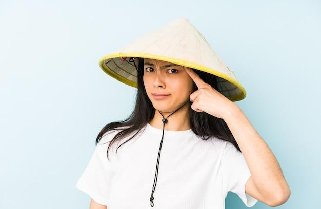 Junge chinesische frau, die ein vietnamesisches heu trägt, das mit dem finger auf sie zeigt, als ob die einladung näher kommt.