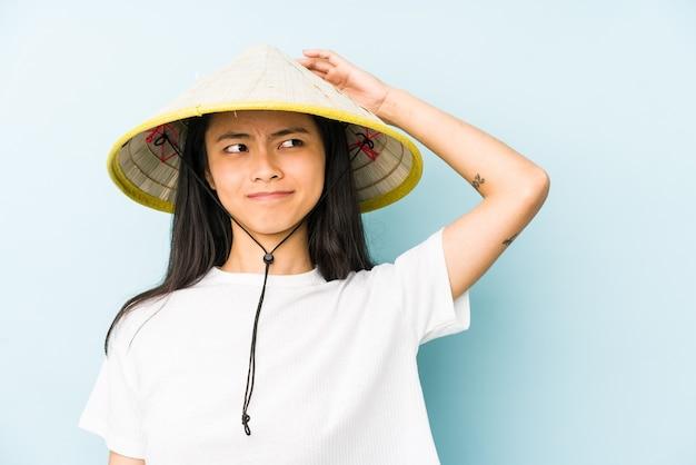 Junge chinesische frau, die ein vietnamesisches heu trägt, das versucht, einem klatsch zuzuhören.