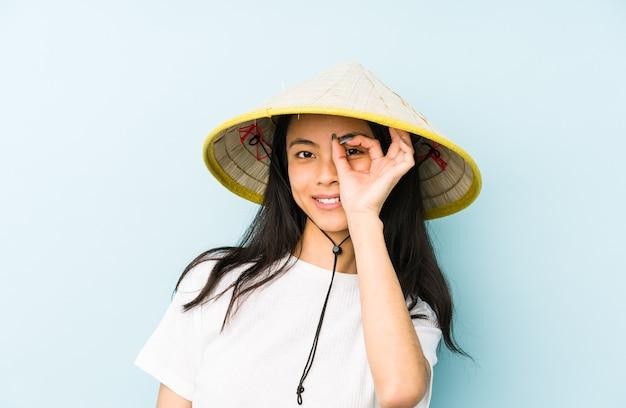 Junge chinesische frau, die ein vietnamesisches heu trägt, isoliert, ein geheimnis zu halten oder um stille zu bitten.