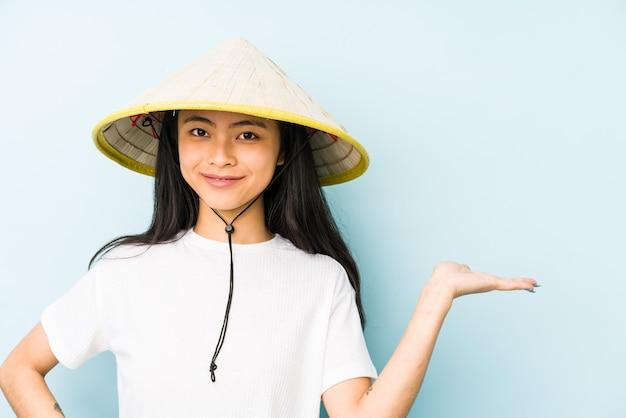 Junge chinesische frau, die ein vietnamesisches heu trägt, isolierte entspanntes denken