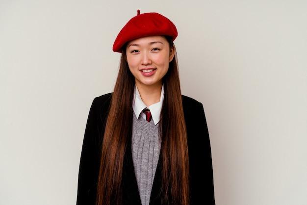 Junge chinesische frau, die eine schuluniform lokalisiert auf weißem hintergrund glücklich, lächelnd und fröhlich trägt.