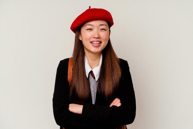 Junge chinesische frau, die eine schuluniform lokalisiert auf weißem hintergrund lacht und spaß hat.