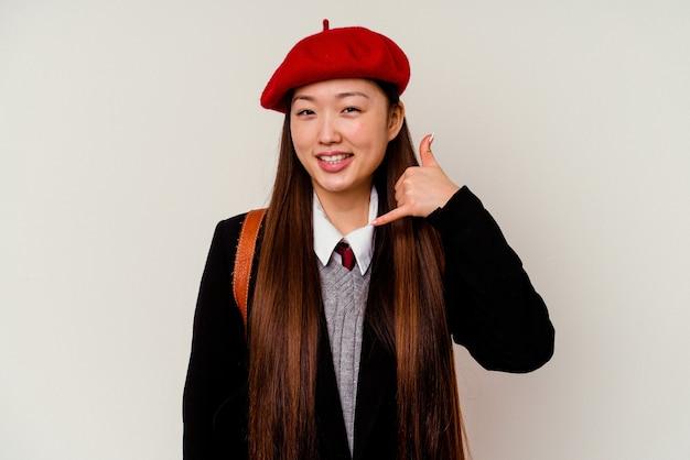 Junge chinesische frau, die eine schuluniform lokalisiert auf weißem hintergrund zeigt, die eine handy-anrufgeste mit den fingern zeigt.
