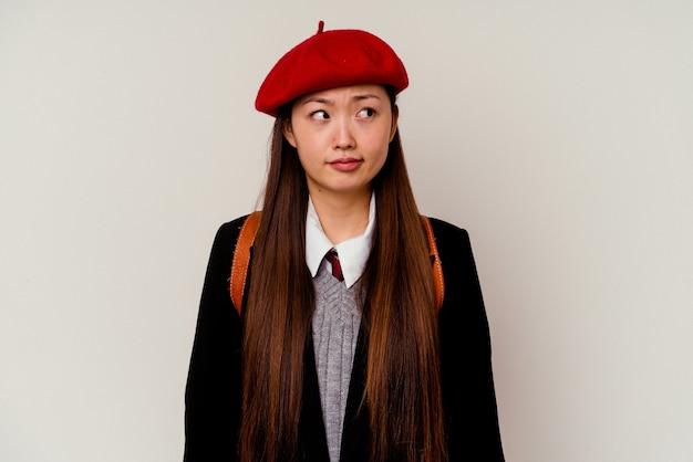 Junge chinesische frau, die eine schuluniform trägt, die auf weißem hintergrund isoliert verwirrt ist, fühlt sich zweifelhaft und unsicher.