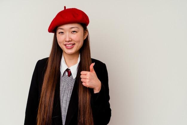 Junge chinesische frau, die eine schuluniform trägt, die auf weißem hintergrund lokalisiert lächelt und daumen hochhebt