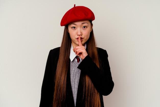 Junge chinesische frau, die eine schuluniform trägt, die auf weißem hintergrund lokalisiert wird, der ein geheimnis hält oder um stille bittet.