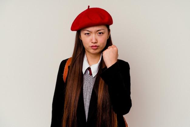 Junge chinesische frau, die eine schuluniform trägt, die auf weißem hintergrund lokalisiert wird, der faust zur kamera, aggressiven gesichtsausdruck zeigt.