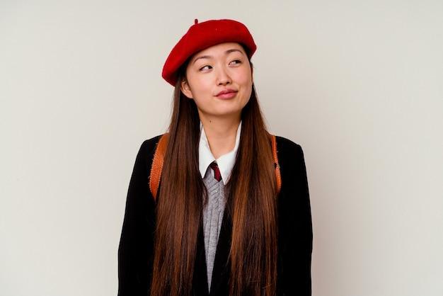 Junge chinesische frau, die eine schuluniform trägt, die auf weißem hintergrund lokalisiert wird und davon träumt, ziele und zwecke zu erreichen