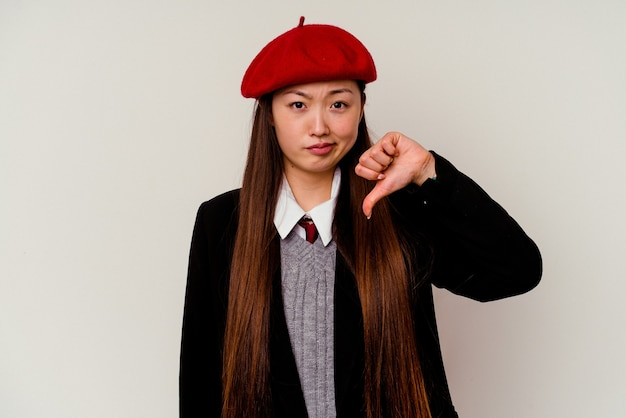 Junge chinesische frau, die eine schuluniform trägt, die auf weißem hintergrund lokalisiert wird und eine abneigungsgeste zeigt, daumen nach unten. uneinigkeit konzept.