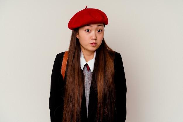 Junge chinesische frau, die eine schuluniform trägt, die auf weißem hintergrund lokalisiert wird, zuckt mit den schultern und offenen augen verwirrt.