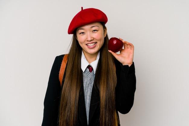Junge chinesische frau, die eine schuluniform trägt, die auf weißem hintergrund lokalisiert wird
