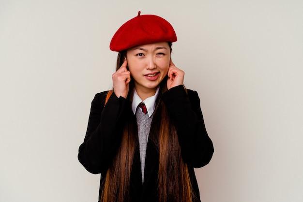 Junge chinesische frau, die eine schuluniform trägt, die auf weißen ohren mit händen bedeckt ist.