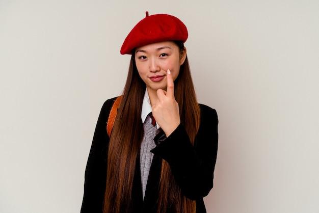 Junge chinesische frau, die eine schuluniform trägt, die mit dem finger auf sie zeigt, als ob die einladung näher kommt.