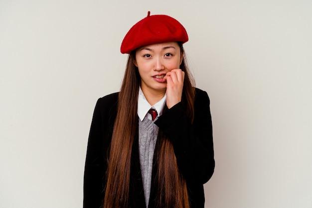 Junge chinesische frau, die eine schuluniform trägt, lokalisiert auf weißem hintergrund beißen fingernägel, nervös und sehr ängstlich.