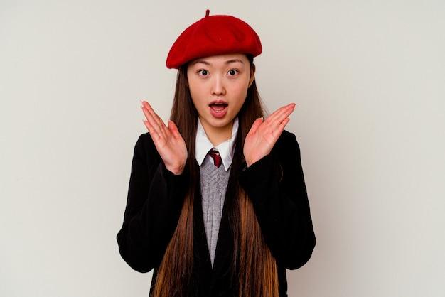Junge chinesische frau, die eine schuluniform trägt, überrascht und schockiert.