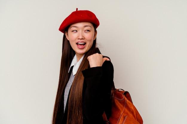 Junge chinesische frau, die eine schuluniform trägt, zeigt mit daumenfinger weg, lachend und sorglos.