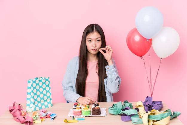 Junge chinesische frau, die einen geburtstag organisiert, lokalisiert mit den fingern auf den lippen, die ein geheimnis halten.