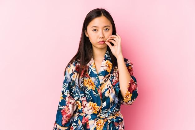 Junge chinesische frau, die einen kimono-pyjama lokalisiert mit den fingern auf den lippen hält ein geheimnis trägt.