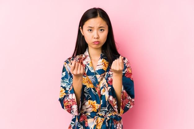 Junge chinesische frau, die einen kimono-pyjama trägt, isoliert zeigt, dass sie kein geld hat.