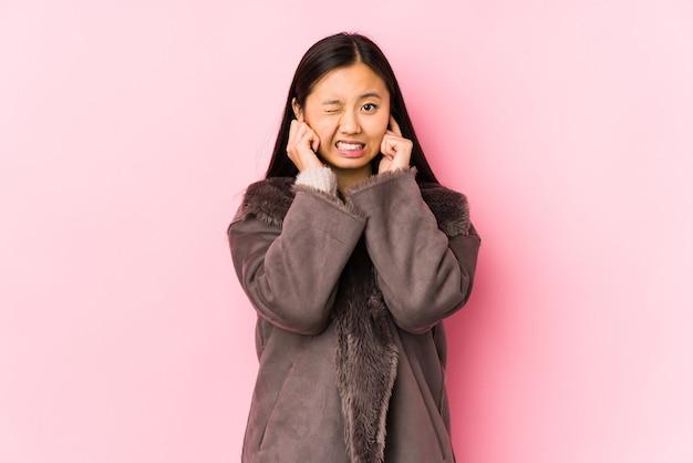 Junge chinesische frau, die einen mantel lokalisiert, der ohren mit händen bedeckt.