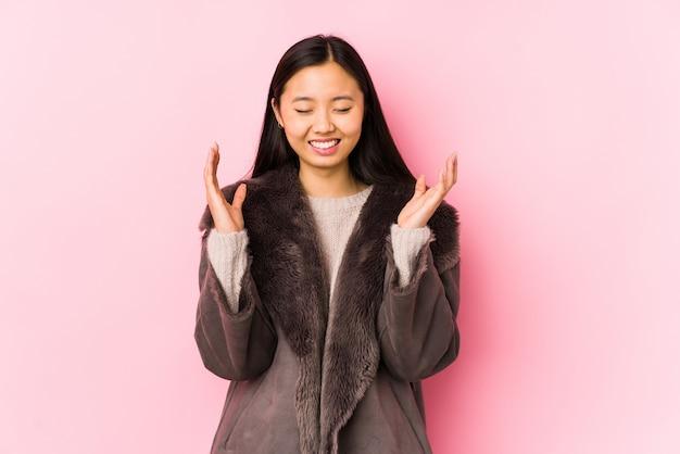 Junge chinesische frau, die einen mantel trägt, isolierte freudiges lachen viel. glückskonzept.