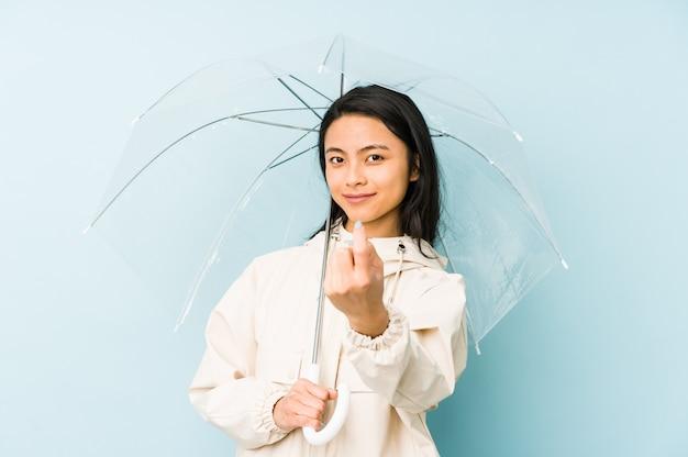 Junge chinesische frau, die einen regenschirm hält, der eine idee hat