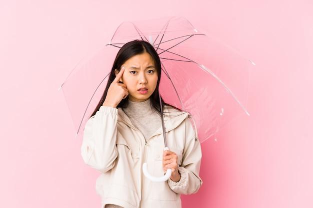 Junge chinesische frau, die einen regenschirm lokalisiert hält, eine enttäuschungsgeste mit dem zeigefinger zeigend.