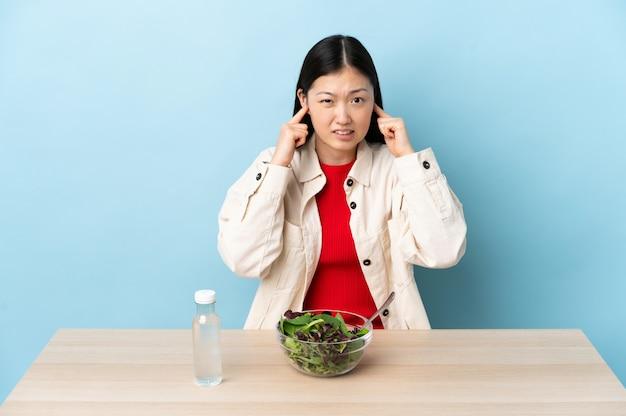 Junge chinesische frau, die einen salat frustriert isst und ohren bedeckt