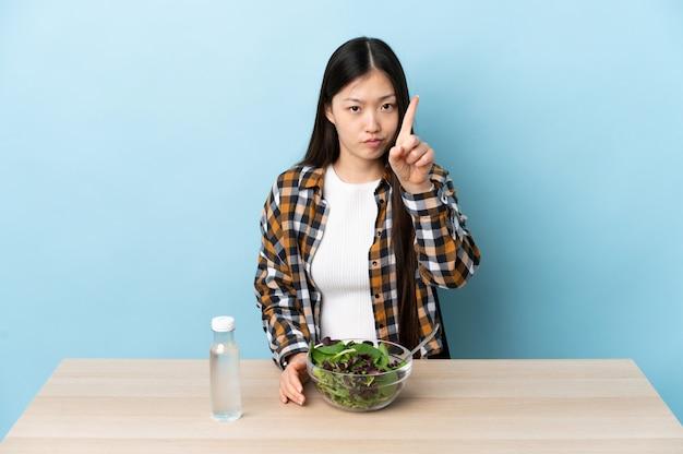 Junge chinesische frau, die einen salat isst, der einen mit ernstem ausdruck zählt