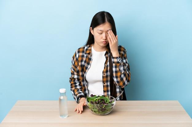 Junge chinesische frau, die einen salat mit kopfschmerzen isst