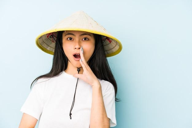 Junge chinesische frau, die einen vietnamesischen heu trägt, isolierte zeigende schläfe mit finger, denkend, konzentrierte sich auf aufgabe.