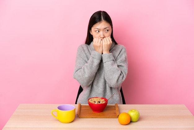 Junge chinesische frau, die frühstück in einem nervösen und ängstlichen tisch der hände zum mund hat