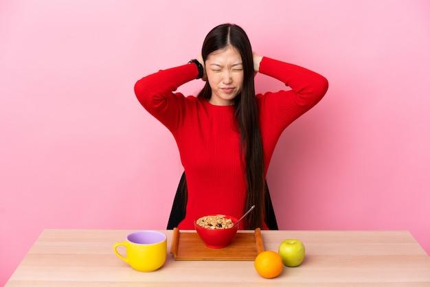 Junge chinesische frau, die frühstück in einem tisch frustriert und ohren bedeckt