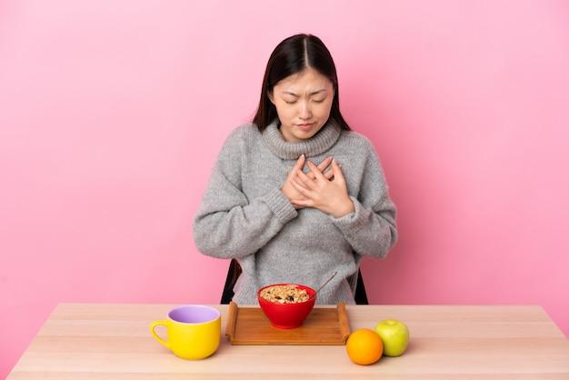 Junge chinesische frau, die frühstück in einem tisch hat, der einen schmerz im herzen hat