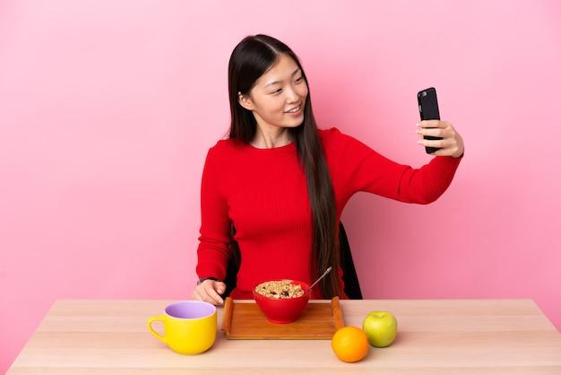 Junge chinesische frau, die frühstück in einem tisch macht, der ein selfie macht