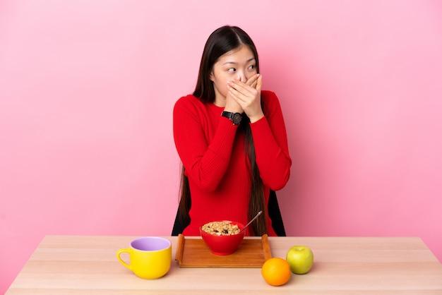 Junge chinesische frau, die frühstück in einer tabelle, die mund bedeckt und zur seite schaut