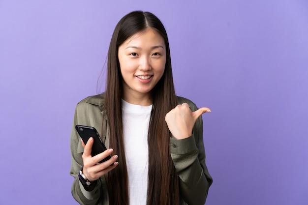 Junge chinesische frau, die handy über isolierte lila wand verwendet, die zur seite zeigt, um ein produkt zu präsentieren