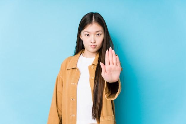 Junge chinesische frau, die in einem blauen hintergrund lokalisiert steht, der mit ausgestreckter hand steht, die stoppschild zeigt, das sie verhindert.