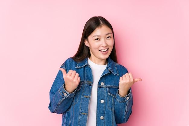 Junge chinesische frau, die in einem rosa isoliert aufwirft, der beide daumen aufhebt, lächelnd und zuversichtlich.