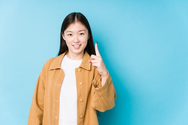 Junge chinesische frau, die in einer blauen wand darstellt, die nummer eins mit finger zeigt.