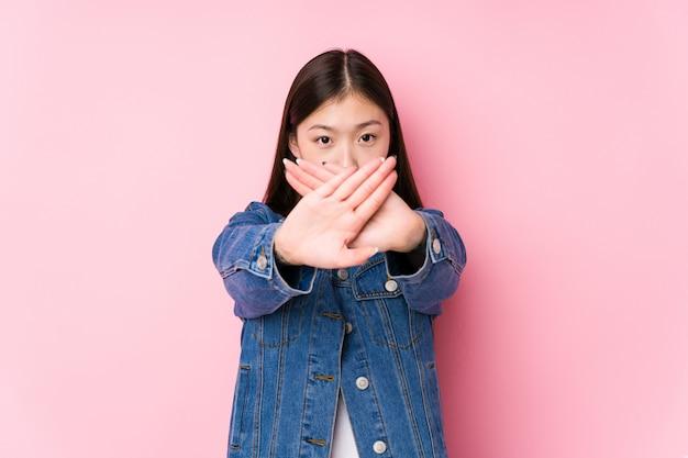 Junge chinesische frau, die in einer rosa wand lokalisiert tut eine ablehnungsgeste aufwirft