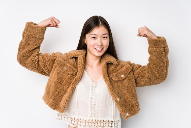 Junge chinesische frau, die in einer weißen wand lokalisiert zeigt, zeigt kraftgeste mit armen, symbol der weiblichen macht