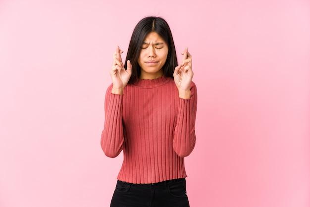 Junge chinesische frau, die isolierte kreuzende finger für das glück aufwirft