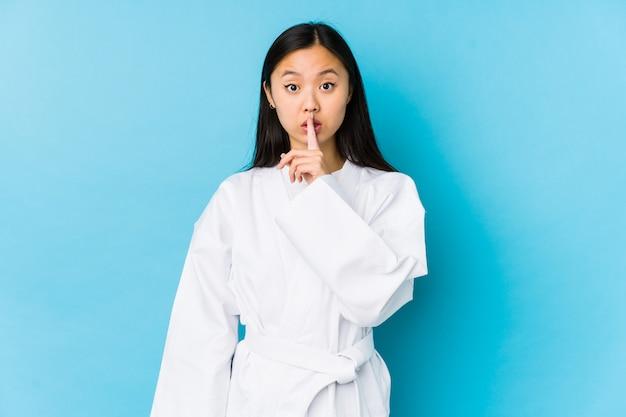 Junge chinesische frau, die karate praktiziert, isoliert, ein geheimnis zu halten oder um stille zu bitten.